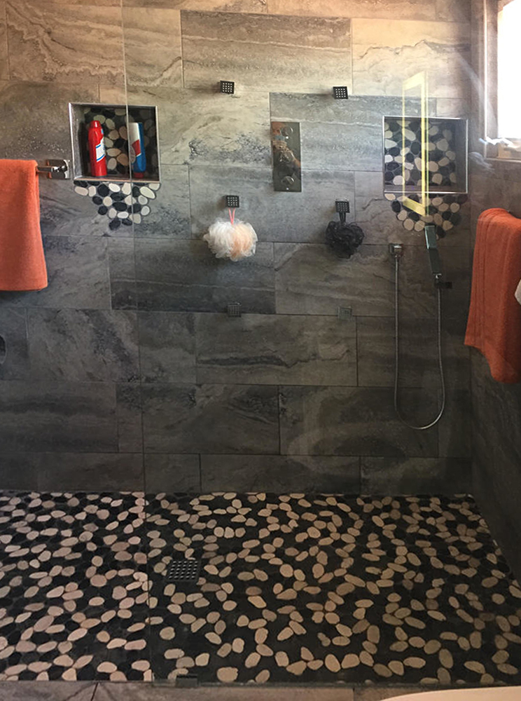 Sliced Black and White Pebble Tile Shower Floor and Niche