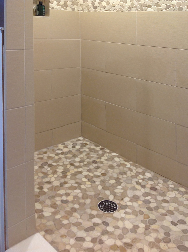 Sliced Tan and White Pebble Tile Shower Flooring and Border